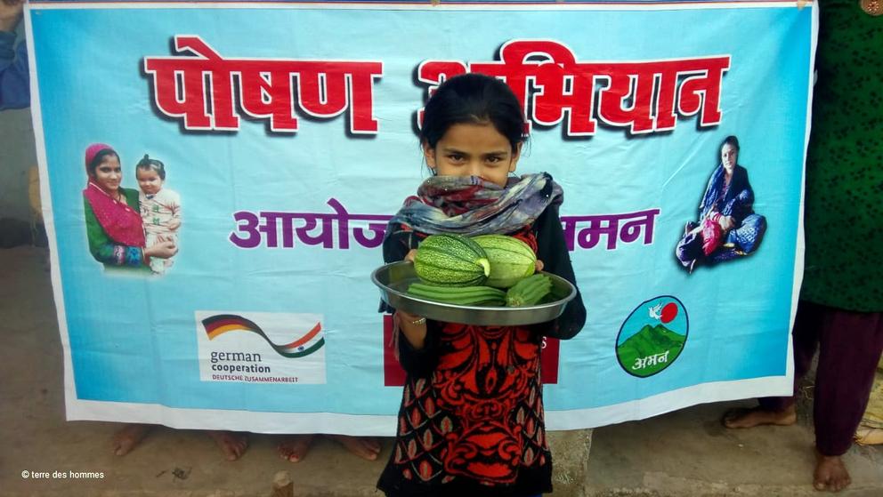 Ein junges Mädchen präsentiert grünes Gemüse.