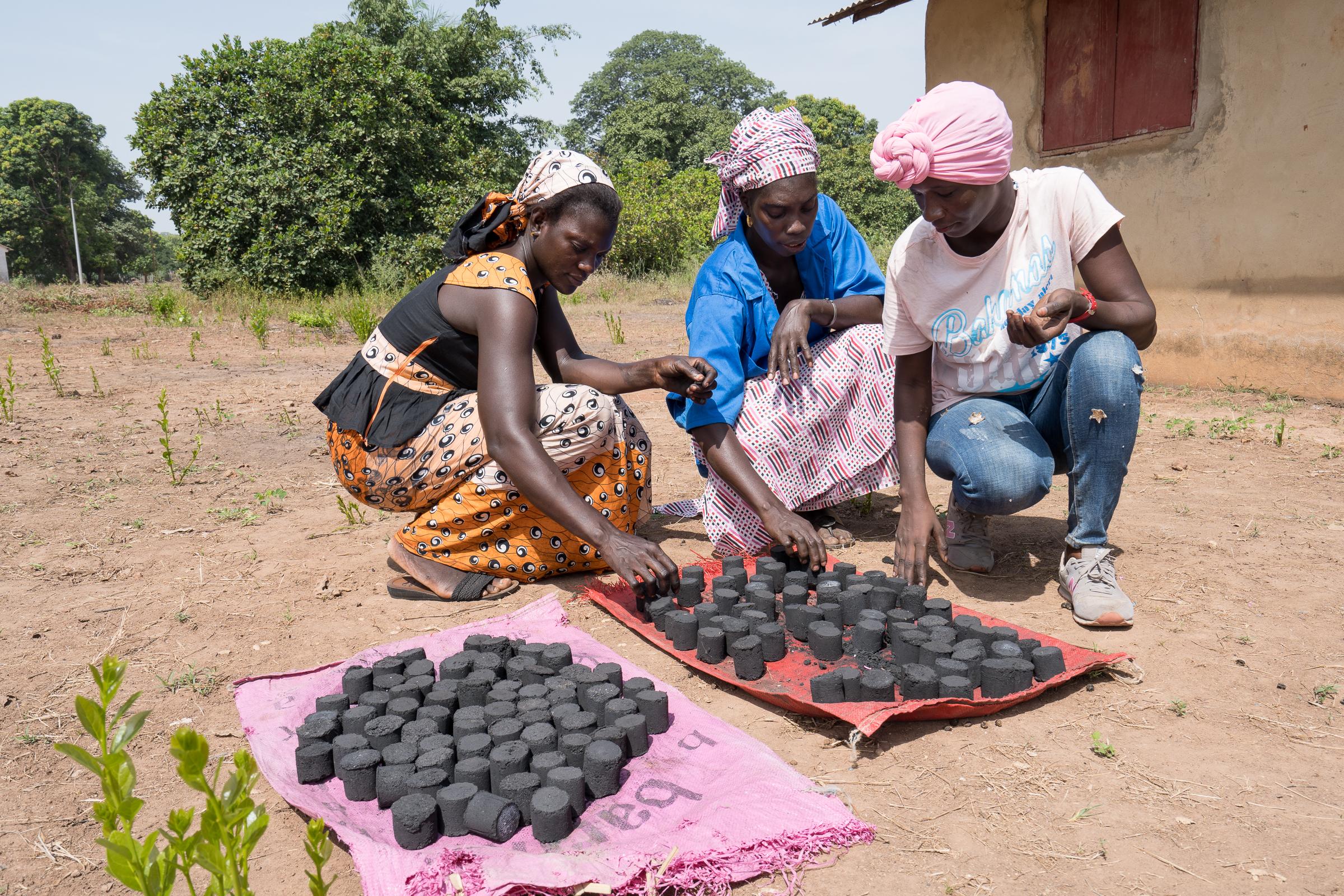 Frauen aus dem Senegal mit selbst hergestellten Kohlebriketts aus nachwachsenden Rohstoffen