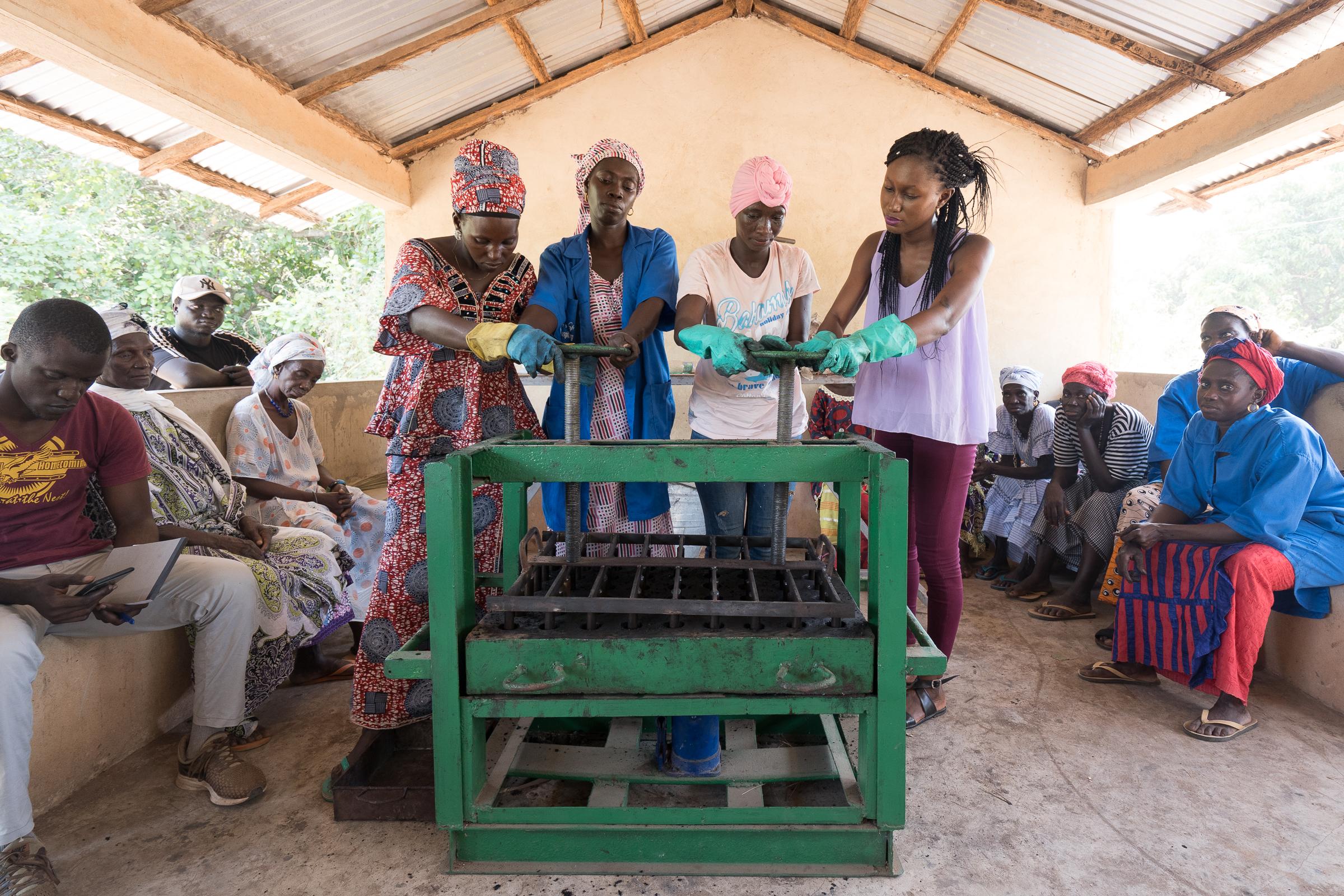 Frauen aus dem Senegal bei der Herstellung von Kohlebriketts aus nachwachsenden Rohstoffen