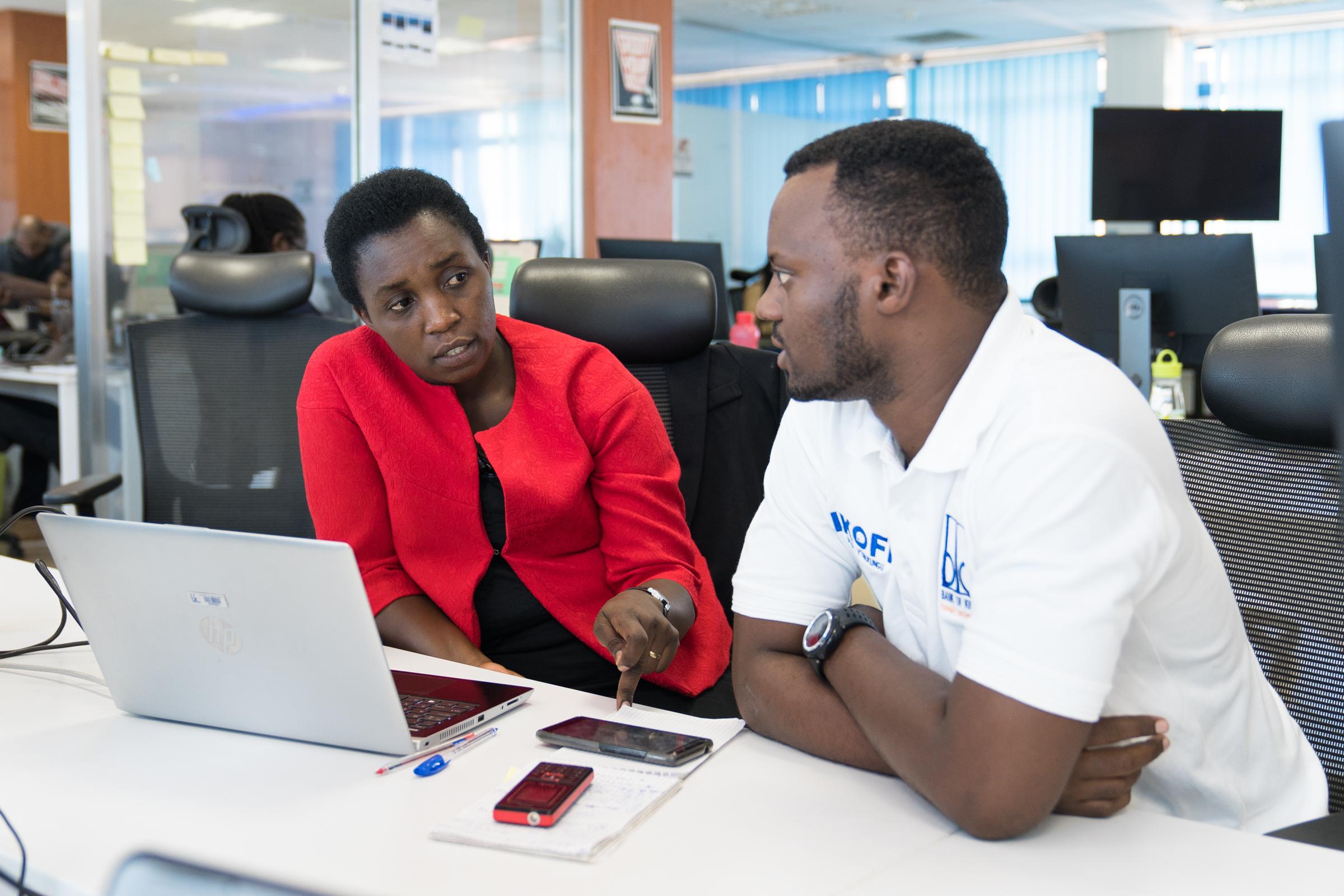 Informatikerin Clothilde Uwineza aus Ruanda im Gespräch mit einem Kollegen am Arbeitsplatz