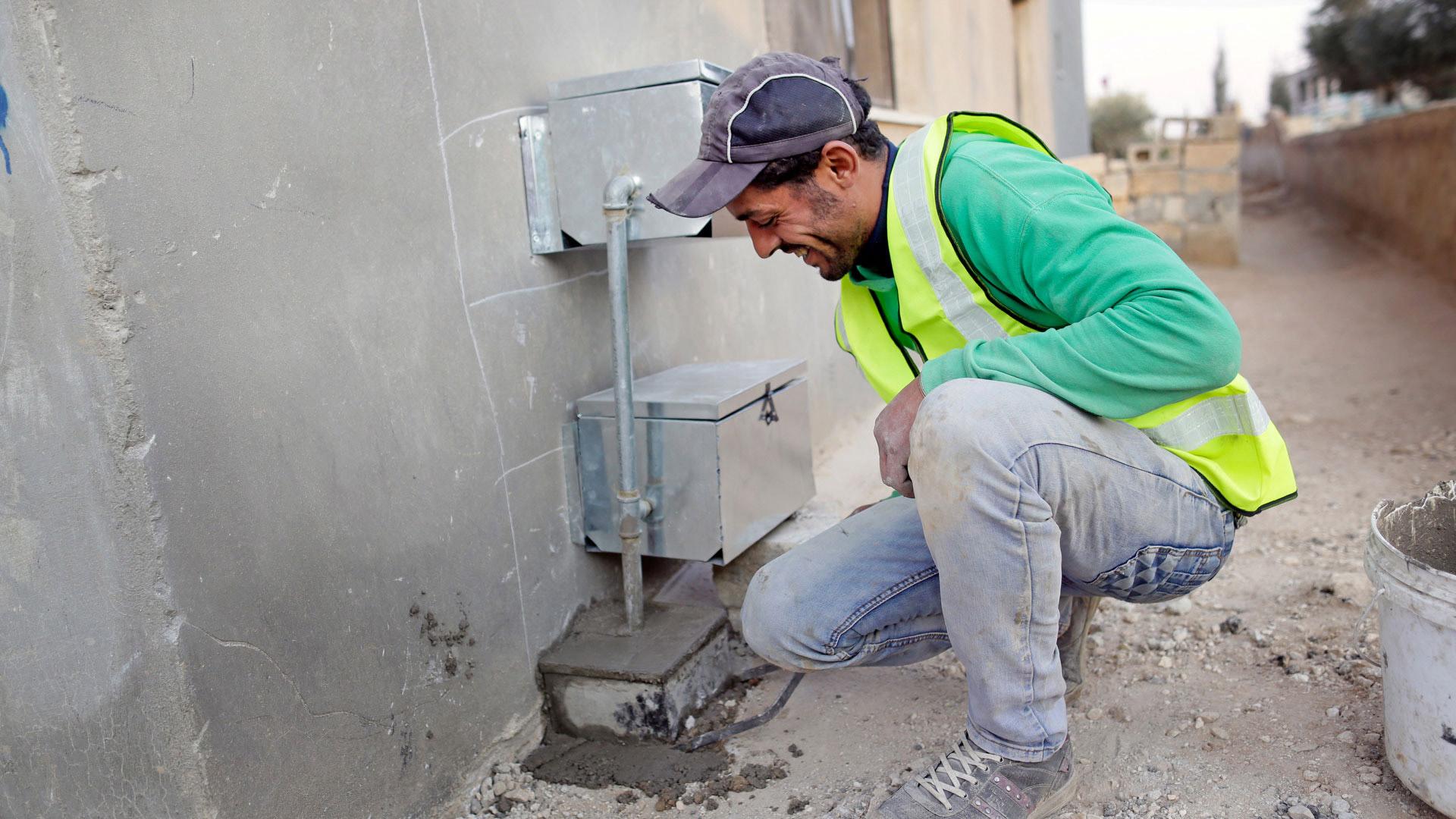 An einem Haus in der Stadt Mafraq in Jordanien werden neue Trinkwasserleitungen verlegt.