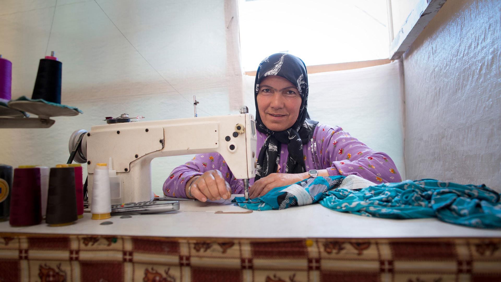 Eine Frau in einem Flüchtlingslager im Libanon kann als Schneiderin etwas Geld für ihre Familie verdienen.