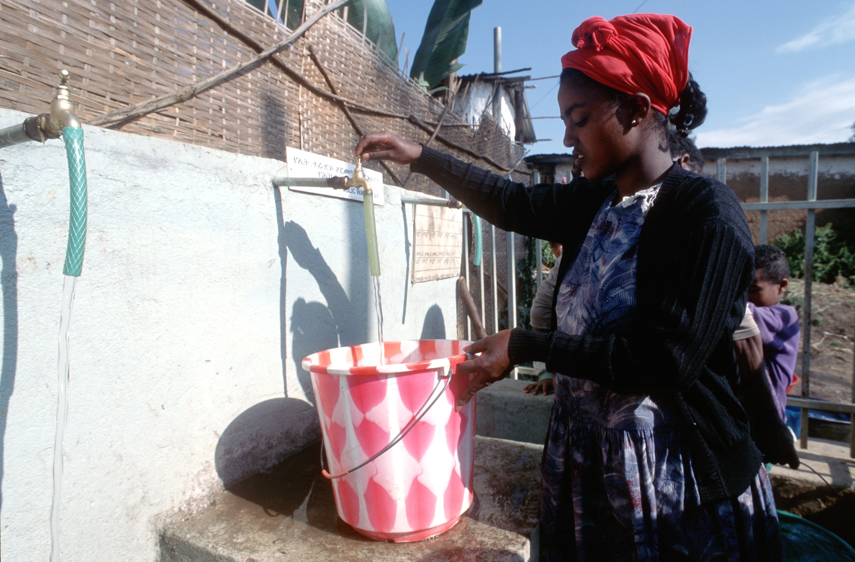 An einer Trinkwasserstelle füllt eine Frau ihren Eimer mit Wasser