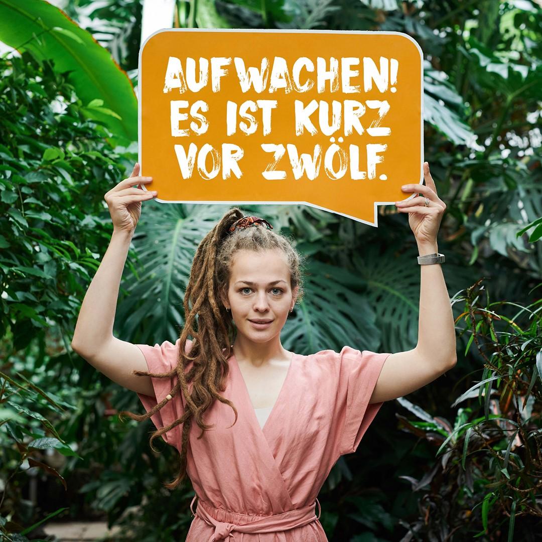 """Bildmotiv zur Mitmachaktion zum Schulwettbewerb für Entwicklung: Eine Frau hält en Schild mit der Beschriftung """"Aufwachen! Es ist kurz vor zwölf."""""""